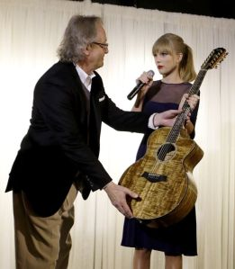 Taylor Swift presents a guitar for display to Kyle Young, director of the Country Music Hall of Fame and Museum, on Saturday in Nashville, Tenn. Swift was at the facility to open the $4 million Taylor Swift Education Center. Photo by Mark Humphrey/The Associated Press